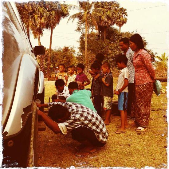 Alcuni cambogiani si precipitano ad aiutare i nostri viaggiatori che hanno appena bucato una ruota