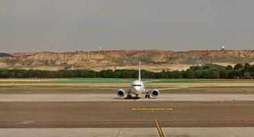 Un passeggero ritardatario insegue il suo aereo sulla pista di atterraggio